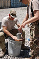 U.S. Navy Lt. Cmdr. Tom Karnowski, left, with Combined Joint Interagency Task Force 435, fills a form with a mixture to make fuel donuts for an Operation Outreach Afghanistan program at Camp Phoenix, Kabul 130728-D-BO405-028.jpg