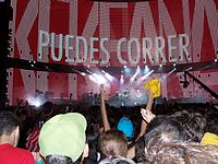 "The view of the stage from the audience's perspective, surrounded by fans, with the words ""PUEDES CORRER"" visible on the video screen. A camera on the right side shows the concert being filmed."