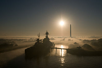 USS Texas (BB-35) - Texas seen at sunrise at the end of 2007; the obelisk in the background is the San Jacinto Monument.