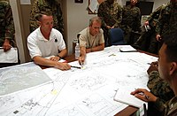 US Navy 040713-N-5055W-051 Mr. Edward Marks, seated, center, role playing as Ambassador for Non-Combative Evacuation Operations (NEO).jpg