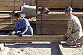 US Navy 041201-M-0757M-014 Builder 2nd Class Darrell Smith, assigned to Naval Mobile Construction Battalion Two Three (NMCB-23), stationed at Al Asad, Iraq, helps an Iraqi student enrolled in the Iraqi Construction Apprentice P.jpg