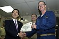 US Navy 050212-N-9389D-056 Commanding Officer, USS Kitty Hawk (CV 63), Capt. Thomas A. Parker, presents a tail hook certificate to Natsuo Yamaguchi, member of the Japan House of Councilors.jpg