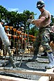 US Navy 050308-N-9712C-001 Builder 3rd Class Peter Lyzack uses a concrete vibrator to fill in hard to get spots in the foundation at a construction project in Okinawa, Japan.jpg