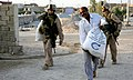 US Navy 070914-M-9152C-045 Hospitalman Rene Cantu and Cpl. Eric Gunlefinger with 3rd Platoon, Echo Company, 2nd Battalion, 6th Marines, Regimental Combat Team 6, help carry a food bag to a Iraqi family while on patrol.jpg