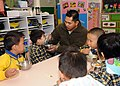 US Navy 081128-N-3262C-124 Chief Fire Controlman Eduardo M. Pareno helps feed a student from the Hong Kong Society for the Protection of Children during a community relations project. The Society serves as a nursery school for.jpg