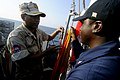 US Navy 100218-N-8335D-232 Quartermaster 3rd Class Jeremy Moore shows Lt. Chum Horn the man overboard Oscar flag aboard USS Patriot (MCM 7).jpg