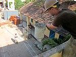 US Navy 100521-N-0827C-001 Builder Constructionman Jose Rivera retrieves a bucket of plaster from a Vietnamese volunteer at the Hope Center engineering site.jpg