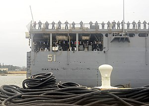 US Navy 111221-N-JP983-005 Sailors assigned to the amphibious dock landing ship USS Oak Hill (LSD 51) man the rails as the ship returns to homeport.jpg