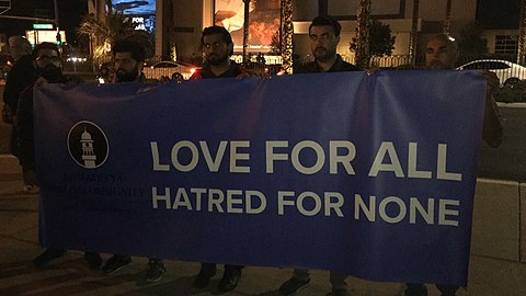 "Men hold a blue banner in the dark that says ""Love for all. Hatred for none."""