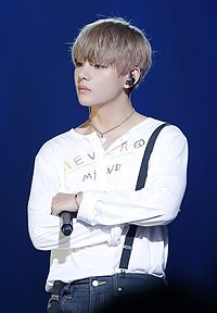 V crosses his arms, his right hand holding a microphone, and looks left