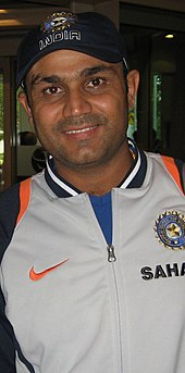 Virender Sehwag wearing a grey jacket and a cap, smiling.