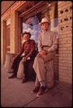 W.G. LEISTIKON, 70, AND JOHN RICKS, 87, IN FRONT OF THE LOCAL DRUGSTORE. STUMPS IN FRONT OF STORE ARE RESERVED FOR... - NARA - 546131.tif
