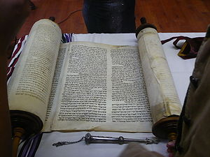 Weekly Torah portion - A Torah scroll and silver pointer (yad) used in reading.