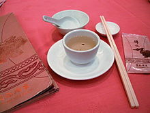 A ceramic spoon in a bowl, pair of chopsticks, plate, and cup of tea