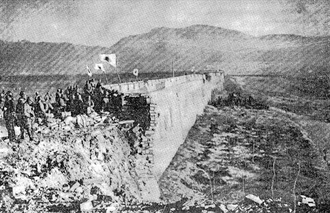 Battle of Nanking - Japanese soldiers stand atop the ruins of Nanking's Zhongshan Gate on December 13 with Zijinshan in the background.
