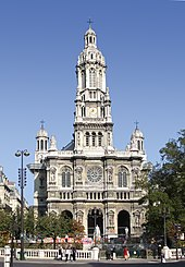 A 19th-century church in the French style, in light coloured stone, with a central tower with rounded top and smaller towers set back to left and right.