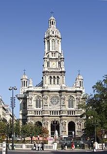En 1800-tals kirke i fransk stil udført i lyse sten med et centralt tårn med rundet top og mindre tårne bagtil i højre og venstre side.