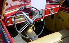Palubní deska Škody 1101 se sdruženým panelem, tříramenným volantem a řadicí pákou na podlaze. Uprostřed mřížka autorádia, pod volantem táhlo ruční brzdy.
