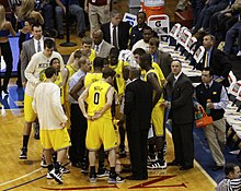 The basketball players standing in maize uniforms and men in suits are huddled around a man in a white shirt and dark pants.