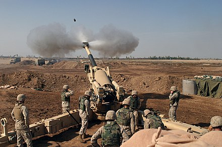 Nine-person crew firing a US M198 howitzer 4-14 Marines in Fallujah.jpg