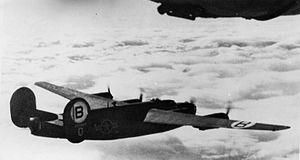 RAF Hardwick - A B-24D Liberator (serial number 42-72869) of the 93rd Bomb Group flies over the cloud layer.
