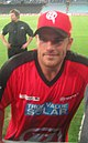 An Australian cricketer wearing a red-black jersey. The cricket field and an another person can be seen in the background.