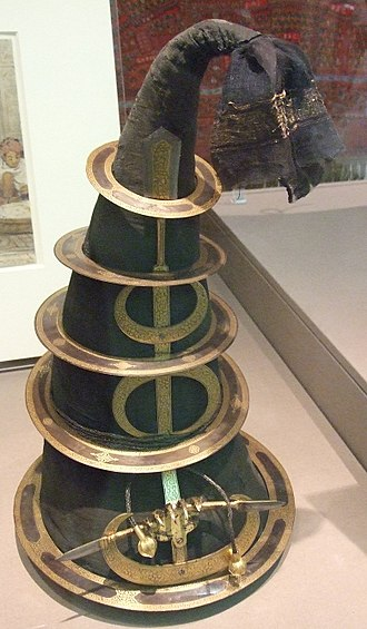 "Chakram - Mid-19th century Nihang turban from Lahore. Cotton over a wicker frame and steel overlaid with gold. ""A tall conical turban provided convenient transportation for a number of sharp steel quoits - edged weapons hurled to lethal effect by the practised hand of the Akalis."""