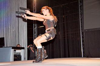 Dual wield - Model dressed as Lara Croft dual wielding pistols