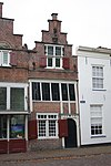 foto van Huis met kleine trapgevel, met in onderpui metselmozaïek. Voormalig gebouw