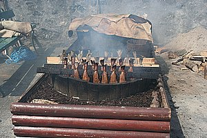 Smoked fish - Racks of haddock in a homemade smoker. Smouldering at the bottom are hardwood wood chips. The sacking at the back is used to cover the racks while they are smoked.