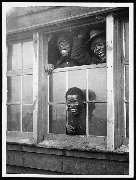 File:At the window of one of their huts (4688531028).jpg