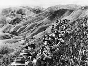 A line of soldiers wearing slouch hats rest amongst tall grass on a slope overlooking a steep valley