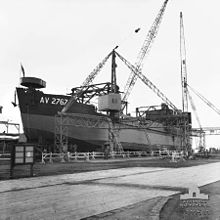 Black and white photo of a ship out of the water surrounded by five cranes