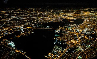Betsy Ross Bridge - Night aerial view of Delaware River crossings from the north. The Betsy Ross Bridge (center) crosses from Bridesburg, Pennsylvania, at the right, to Pennsauken Township, New Jersey, at left and upper center.  The Tacony–Palmyra Bridge is visible at the lower left, and the Benjamin Franklin Bridge is in the distance at upper right.