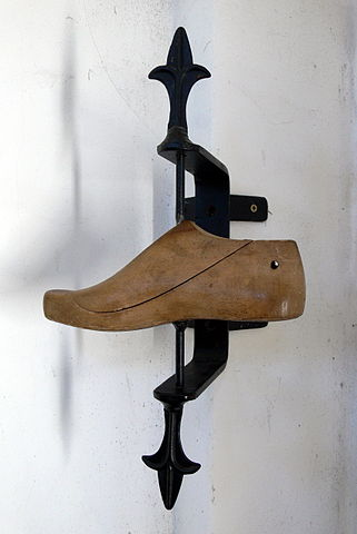 A wooden shoe last on an iron pivot
