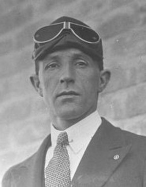 Collar pin - Norman Brearley, Australian aviation pioneer is shown in a photograph of the 1920s.  The head and shoulders image show him wearing flying goggles, a day suit, tie and collar pin.