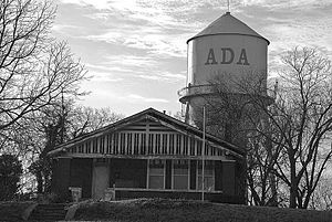 Ada, Oklahoma - Picture taken on Broadway of the former Stout family residence with one of the city's water towers behind it.