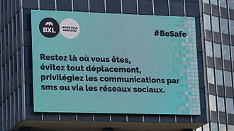 "2016 Brussels bombings - Digital billboard in Brussels. It reads, in French, ""Stay where you are, avoid all movement, prioritise communications by SMS or social networks."""