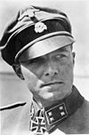 A black-and-white photograph of a man wearing a military uniform, peaked cap and a neck order in shape of an Iron Cross. His cap has an emblem in shape of a human skull and crossed bones.