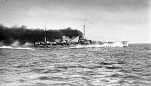 A large gray warship steams at full speed; thick black smoke pours from its two funnels.