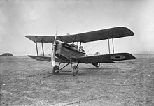 Three-quarter view of military biplane on landing ground