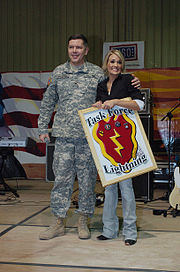 Underwood receiving a gift from the 25th Infantry Division (Task Force Lightning) after performing in Tikrit, Iraq in December 2006.