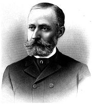chest high portrait in a suit with mustache and beard