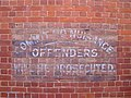 Commit No Nuisance sign painted on the side of the Masonic Hall.jpg