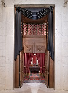 The courtroom doors of the Supreme Court draped in black. Through the open doors is visible Ginsburg's seat and the bench before the seat, each also draped in black.