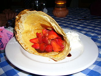 A sweet crêpe served with strawberries and whi...