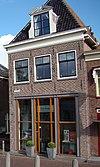 foto van Hoekhuis met verdieping en schilddak. Pui modern. Dakkapel met gebroken fronton
