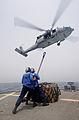 Defense.gov News Photo 110715-N-XQ375-398 - Seaman Matt Binnie left and Seaman Lucio Robles prepare to attach a cargo net to an MH-60S Sea Hawk helicopter during a vertical replenishment.jpg