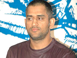 The face and shoulders of Mahendra Singh Dhoni wearing a brown-coloured t-shirt.