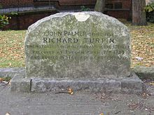 A stone gravestone with a curved top, with several lines of inscription. Trees, grass, and a wall are visible in the distance.